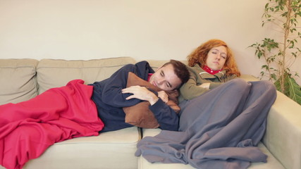 Couple having a cold and resting on the sofa