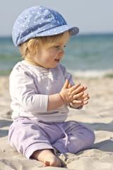 Happy baby girl on beach.