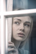 Beautiful woman looking by the window.