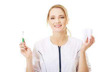 Young dentist with toothbrush and tooth model.