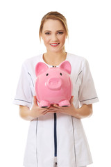 Young female doctor holding a piggybank.
