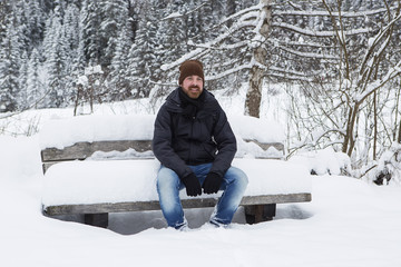 Young man is sitting on a snowy park bench