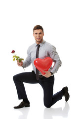 Man kneeling with red rose and heart balloon.