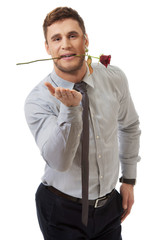 Handsome man holding red rose in his mouth.