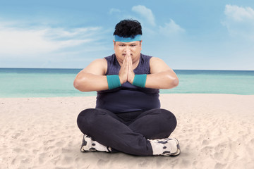 Overweight man doing yoga on beach 1
