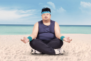 Overweight man doing yoga on beach