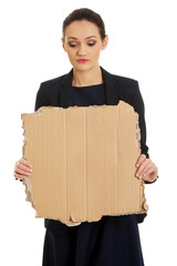 Sad businesswoman with piece of cardboard.