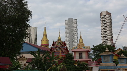 buddha temple at the background of hight new skyscrapers