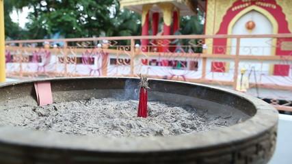 red fragrance sticks burn against Buddha temple