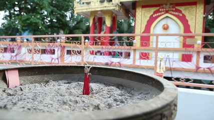 red fragrance sticks burn against Buddha temple