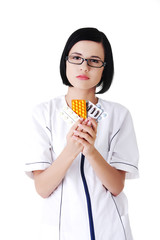 Female doctor in uniform holding pills