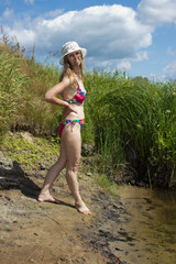 Woman in a swimsuit standing on the river bank
