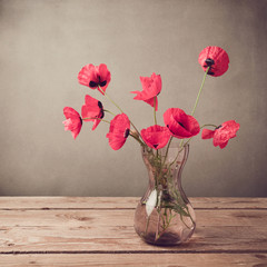 Poppies in vase over vintage background