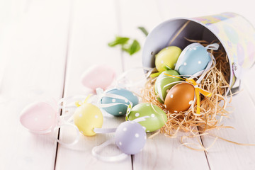 Pastel colored Easter eggs over white wooden background