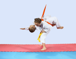 Children athletes are training on the mat