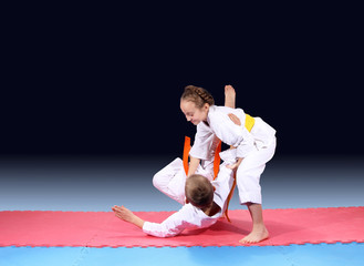Girl and boy are trained judo throw on the mat