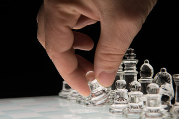 Hand holding the  pawn to make the first move