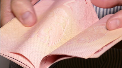 man's hands turning the pages of the passport with visas and sta
