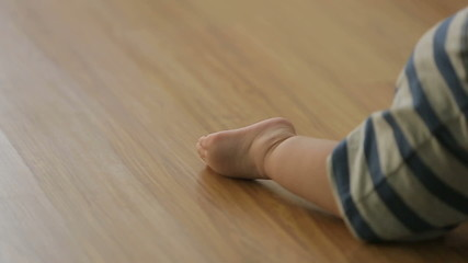 a little funny baby crawling on the floor, back view