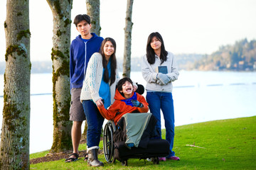 Disabled little boy in wheelchair surrounded by brother and sist