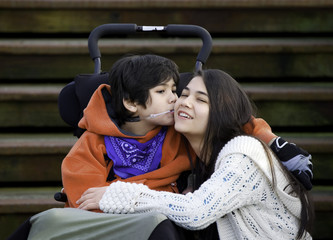 Disabled little boy kissing his big sister on cheek while seated