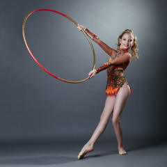 Adorable young gymnast performing with hoop