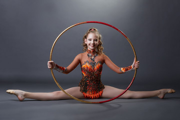 Happy flexible gymnast posing with hoop