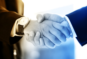 Handshake of two businessmen on an abstract background