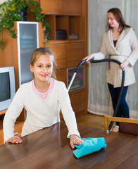 Woman and girl cleaning at home