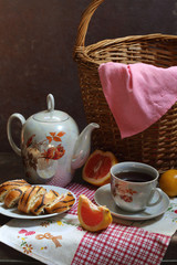 Tea with a swiss roll and grapefruit