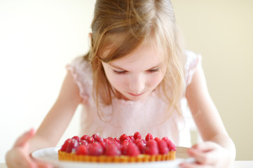 Adorable little girl and a raspberry cake