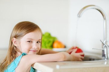 Adorable little girl washing vegetables