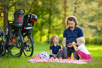 Young father and his daughters having a picnick