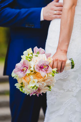 Close up of bride holding beautiful wedding flowers bouquet with