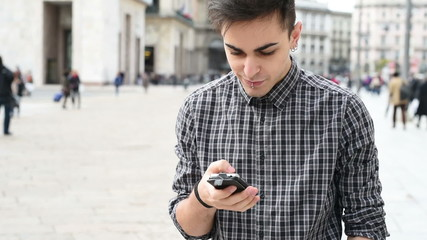 young handsome alternative model man in town using smartphone
