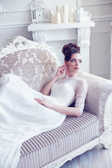 Young gorgeous bride is sitting in antique couch