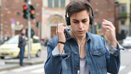 young handsome alternative dark model man in town listening to m