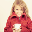 portrait of a cute little girl in red sweater holding a mug in h
