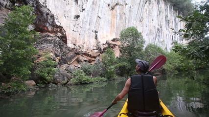 elder strong man rows kayak along river past grey rocks