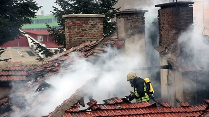 A burning house roof top and a firefighter