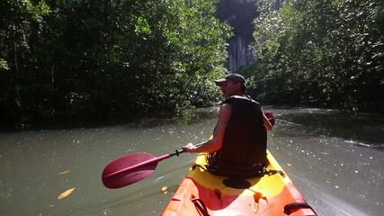 strong elder man rows kayak turns aside and speak