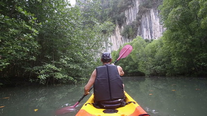 strong elder man floats kayak to gray cliff