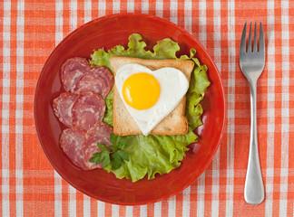 Fried heart shaped egg on toast with salad and chorizo sausage f