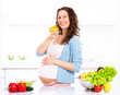 Pregnant young woman eating apple. Healthy food