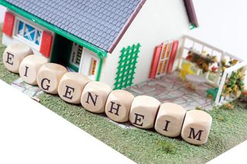 Haus und Holzwürfel mit dem Wort Eigenheim