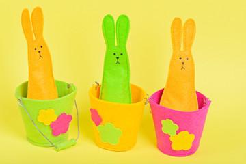 Three easter Bunnies in buckets on yellow