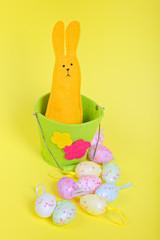 Easter rabbit in bucket on yellow