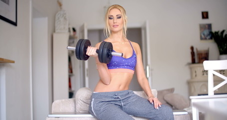 Sexy sporty blond woman exercising with weights
