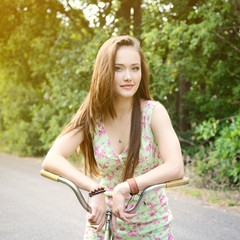 Happy young beautiful woman with retro bicycle. Portrait of fres