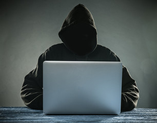 A hacker with a hood with laptop